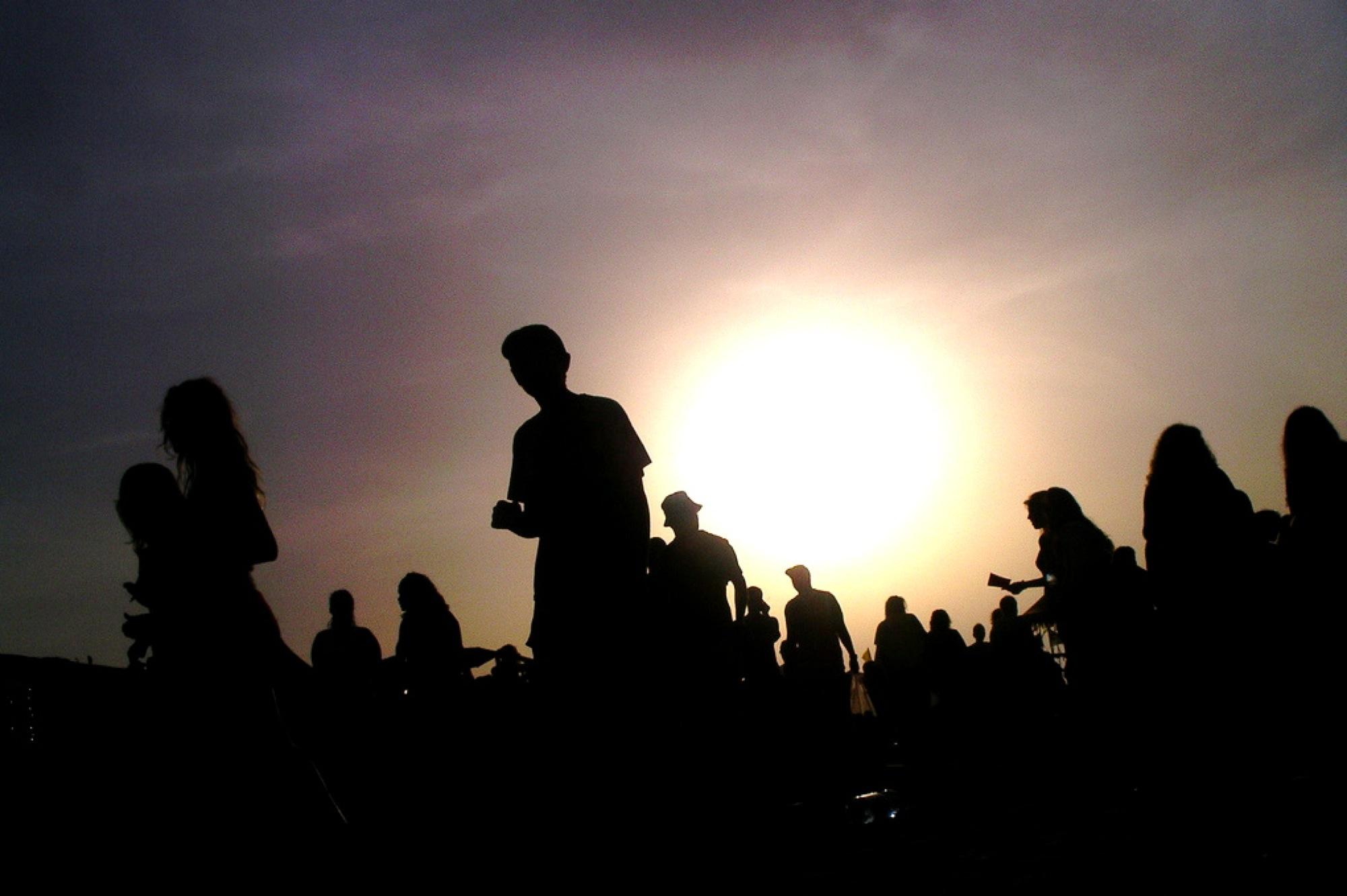 Mange mennesker med stor sol i bakgrunn