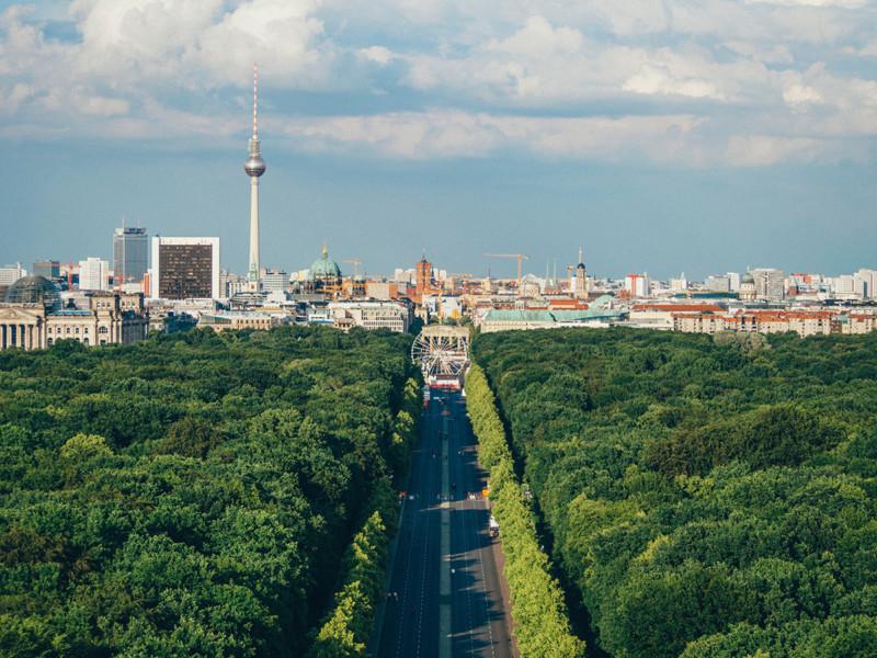 Utsikt mot by, med stort grøntområde i front med trær. Vei i midten av bildet med pariserhjul i midten av bildet.